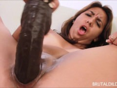 Brunette bringing her pussy to a wet orgasm with two big brutal dildos