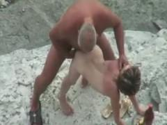 Camra gets old guy banging young girl on the beach